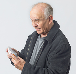 Man reading box of over-the-counter medication.